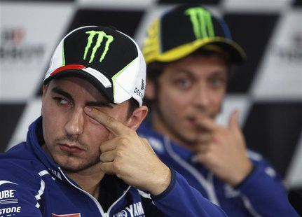Yamaha MotoGP rider Jorge Lorenzo of Spain (L) rubs his eye as his teammate Valentino Rossi of Italy watches during the post-qualifying news