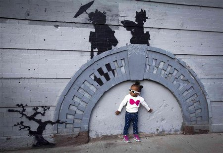 A child poses for a photo under a new art piece by British graffiti artist Banksy in the Brooklyn borough of New York, October 17, 2013. REU