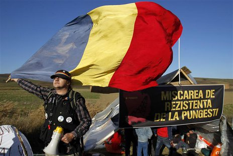 A man holds Romania's national flag in front of a tent installed on the empty lot where U.S. oil major Chevron plans to search for shale gas