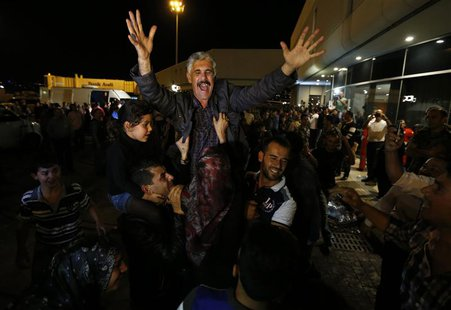 One of the nine newly released Lebanese hostages, who were held by rebels in northern Syria, gestures as he is welcomed by his relatives upo