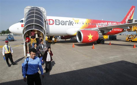 Vietjet Air passengers exit the aircraft after arriving at Tan Son Nhat airport in Vietnam's southern Ho Chi Minh city October 20, 2013. REU