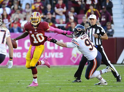 Oct 20, 2013; Landover, MD, USA; Washington Redskins quarterback Robert Griffin III (10) scrambles to avoid the tackle by Chicago Bears defe