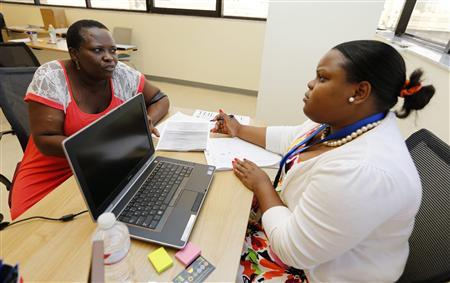 Certified Application Counselor Sheslie Caze (R) takes information from a woman who asked not to be identified as she inquired about the Affordable Care Act insurance, commonly referred to as Obamacare, at the Borinquen Medical Center in Miami, Florida October 1, 2013.  REUTERS/Joe Skipper