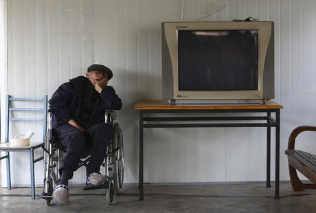 A man sleeps on a wheelchair next to a television set at a nursing home on the Double Ninth Festival, or Chongyang Festival, in Kunming, Yun
