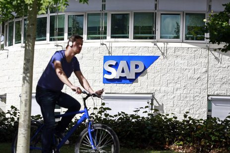 A man cycles past the SAP logo at its offices in the CityWest complex, Dublin September 5, 2013. REUTERS/Cathal McNaughton