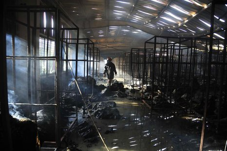 A firefighter inspects a burnt garment factory after a fire in the Bangladeshi town of Gazipur, 40 km (25 miles) north of Dhaka October 9, 2