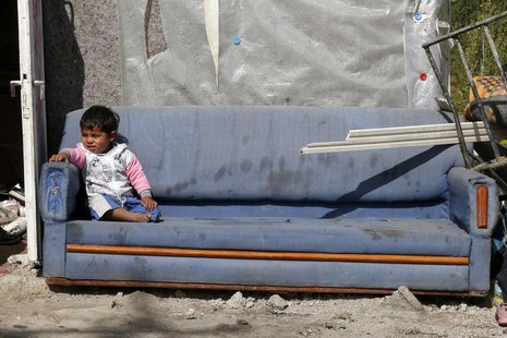 A Syrian refugee boy sits on a couch collected from garbage in central Ankara October 5, 2013. REUTERS/Umit Bektas