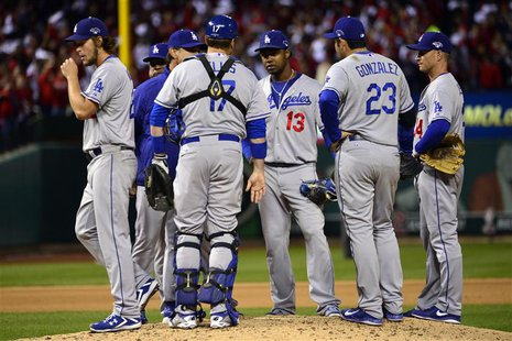 Oct 18, 2013; St. Louis, MO, USA; Los Angeles Dodgers starting pitcher Clayton Kershaw (left) walks back to the dugout after being relieved