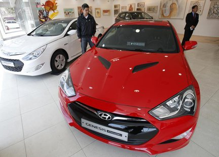 People look around as Hyundai Motor's Genesis (front) and Sonata are displayed at a gallery-style Hyundai dealership in Seoul April 5, 2012.