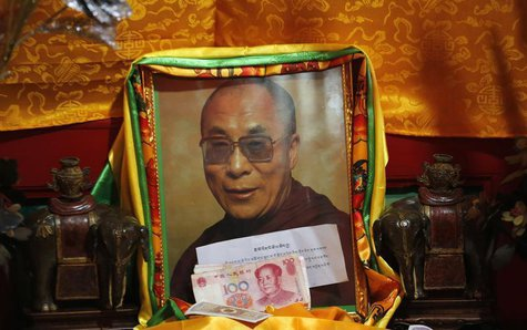 Chinese bank notes from faithful are placed in front of a portrait of Tibetan spiritual leader Dalai Lama at Kumbum monastery, where Dalai L