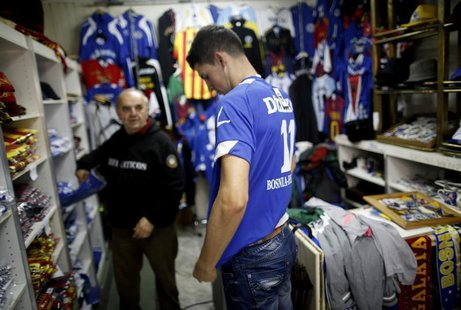 A tourist tries on a Bosnian national soccer team jersey at a shop in the old part of the city, Bascarsija, in Sarajevo, October 16, 2013. R