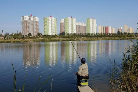 A resident fishes at a lake near apartment blocks in Beijing October 20, 2013. REUTERS/Jason Lee