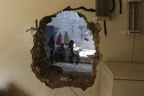 A Free Syrian Army fighter aims his weapon as he is seen through a hole in a wall in Aleppo's Karm al-Jabal district October 21, 2013. REUTE