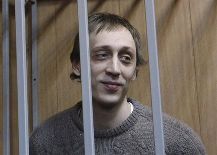 Dancer Pavel Dmitrichenko looks out from the defendant's holding cell during a hearing in Moscow October 22, 2013. REUTERS/Maxim Shemetov