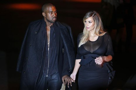 U.S. musician Kanye West (L) and companion Kim Kardashian arrive at the Givenchy Spring/Summer 2014 women's ready-to-wear fashion show durin