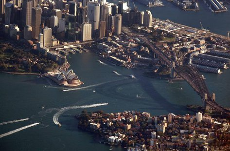 The Sydney Harbour Bridge casts a shadow next to the Sydney Opera House and central business district (CBD) as boats make their way along th