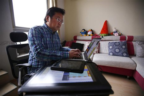 Chinese cartoonist Wang Liming uses his computer inside his apartment before an interview with Reuters in Beijing, Ocotober 22, 2013. REUTER