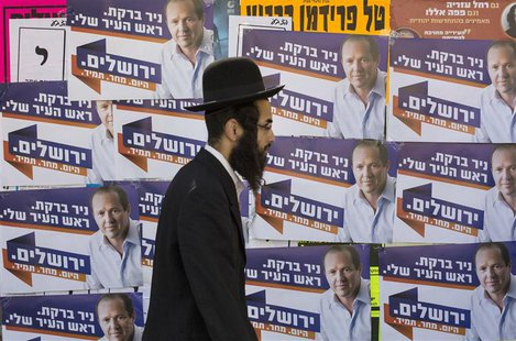 An ultra-Orthodox Jewish man walks past municipal elections campaign posters of Jerusalem Mayor Nir Barkat in Jerusalem October 22, 2013. RE