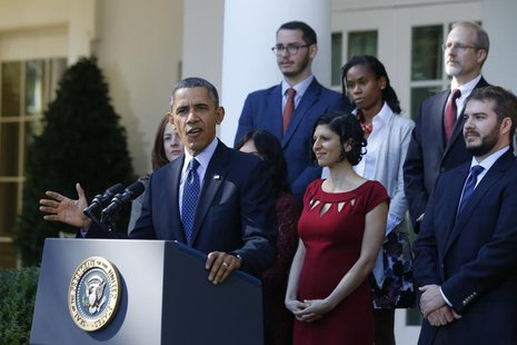 U.S. President Barack Obama stands with Affordable Care act registrants and beneficiaries as he speaks about healthcare from the Rose Garden