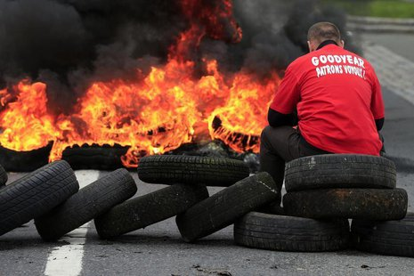 Flames and smoke rise from burning tyres as a worker sits on a barricade blocking the entrance of U.S. tyre-maker Goodyear's plant to protes