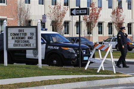 A police officer guards the entrance to the high school in Danvers, Massachusetts October 23, 2013. A 14-year-old student at a suburban high school outside Boston was in custody Wednesday after police found the body of a teacher in the woods behind the school overnight, officials said.  REUTERS/Brian Snyder