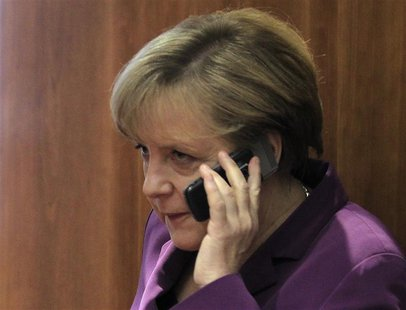 Germany's Chancellor Angela Merkel uses her mobile phone before a meeting at a European Union summit in Brussels in this December 9, 2011 fi