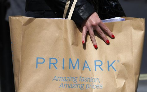 A shopper passes demonstrators outside clothing retailer Primark in London April 27, 2013. REUTERS/Suzanne Plunkett