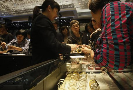 A sales attendant shows a gold bracelet to customers leaning over a half-empty display case at a jewellery store in Hong Kong April 26, 2013