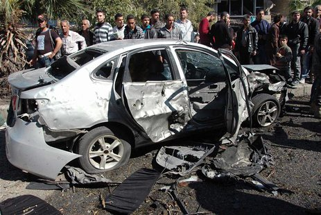 People gather around the wreckage of a car after a car bomb exploded in al-Ahram street near al-Nuzha roundabout in Homs, in this handout di