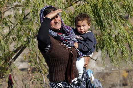 A Syrian refugee carries her baby in central Ankara October 20, 2013. REUTERS/Umit Bektas