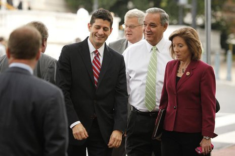 U.S. Representative Paul Ryan (R-WI) (L) smiles and talks with fellow House Republicans as they arrive for meetings at the Republican Nation