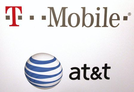 AT & T and T-Mobile logos are seen posted on the wall of a subway station at West 14th street and 8th avenue in New York September 27, 2011.