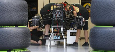 Mechanics work on the car of Lotus Formula One driver Romain Grosjean of France at the pit ahead of the Singapore F1 Grand Prix in this Sept