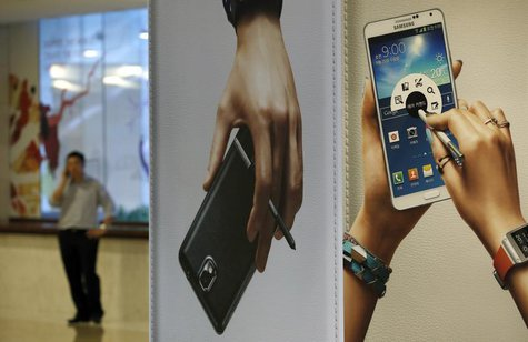 A man talks on his mobile phone near advertisements promoting the Samsung Electronics' Galaxy Note 3 at the company's headquarters in Seoul