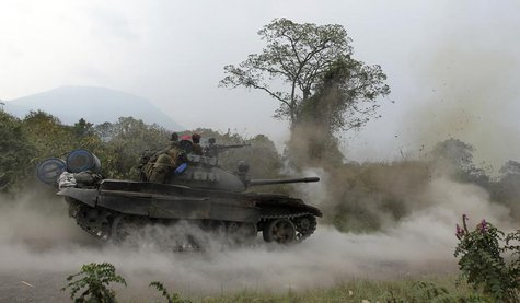 A Congolese armed forces (FARDC) tank fires a shot as soldiers battle M23 rebels in Kibati, outside Goma in the eastern Democratic Republic