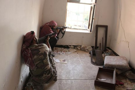 Free Syrian Army fighters take position as they aim their weapons inside a room in Bab Antakya district in Old Aleppo, October 22, 2013. Pic