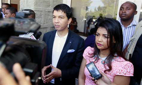 Madagascar's President Andry Rajoelina (C) flanked by his wife Mialy address the media after casting their ballots at a polling centre in Am