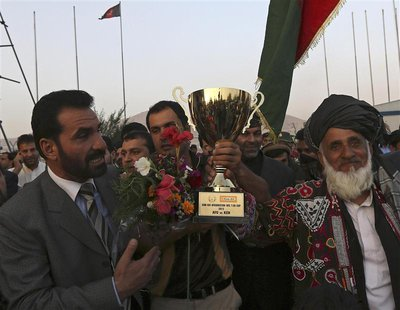 Afghan cricket team captain Mohammad Nabi Esa Khil (C) holds the ACC Cup after the team's arrival in Kabul, in this October 12, 2013 file ph