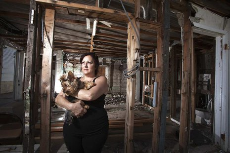 Christine Cina poses for a portrait in what is left of her house after Superstorm Sandy in the Staten Island borough of New York, September