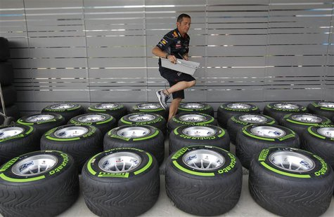 A team member walks amid Pirelli tyres outside the Red Bull garage at the Buddh International Circuit in Greater Noida on the outskirts of N
