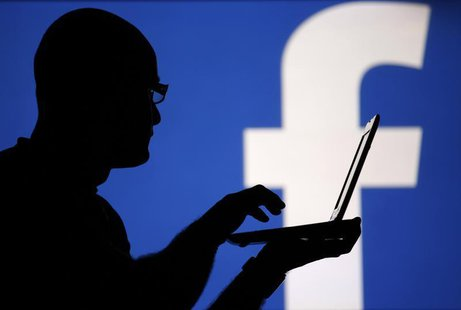A man is silhouetted against a video screen with an Facebook logo in this photo illustration taken in the central Bosnian town of Zenica, Au