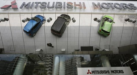 Mitsubishi Motors Corp's vehicles and a passer-by are reflected on an external wall at the company headquarters in Tokyo May 23, 2013. REUTE