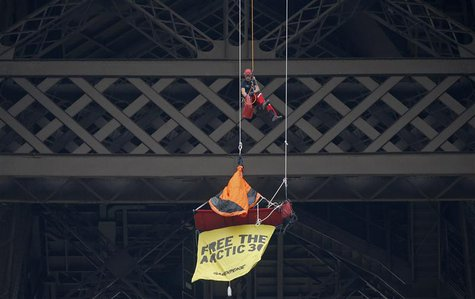 A French firefighter (top) approaches a Greenpeace activist hanging from the second floor of the Eiffel Tower in Paris, October 26, 2013. RE
