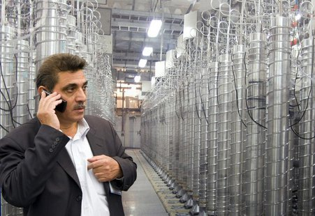 An official from Iran's Atomic Energy Organization speaks on his mobile phone in front of uranium enriching centrifuges at an exhibition of