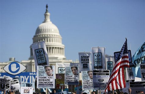 "Demonstrators hold up their signs during the ""Stop Watching Us: A Rally Against Mass Surveillance"" march near the U.S. Capitol in Washington"