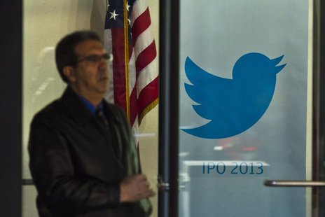 A man walks past a Twitter banner while leaving JP Morgan headquarters, before Twitter's IPO in New York October 25, 2013. REUTERS/Eduardo M