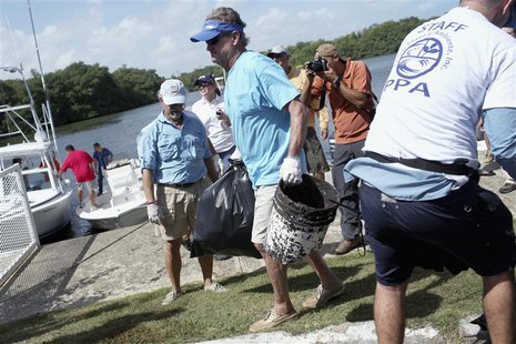 "U.S. artist and conservationist Guy Harvey (C) leads a group of volunteers along the San Juan estuary system for the second ""mega cleanup"" o"