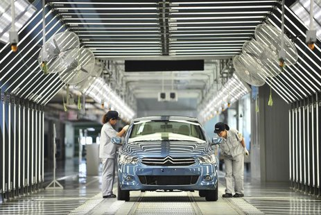 Employees work at the third factory of Dongfeng Peugeot Citroen Automobile company, after its inauguration ceremony, in Wuhan, July 2, 2013.