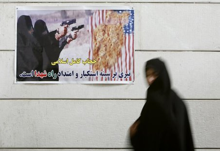 An Iranian woman walks past an anti-U.S. poster during a visit to a war museum in the city of Khorramshahr, 1350 km (844 miles) southwest of