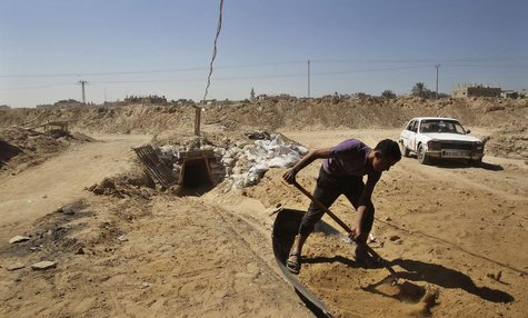A tunnel worker shovels sand outside a smuggling tunnel on the border between Egypt and the southern Gaza Strip October 8, 2013. REUTERS/Ahm